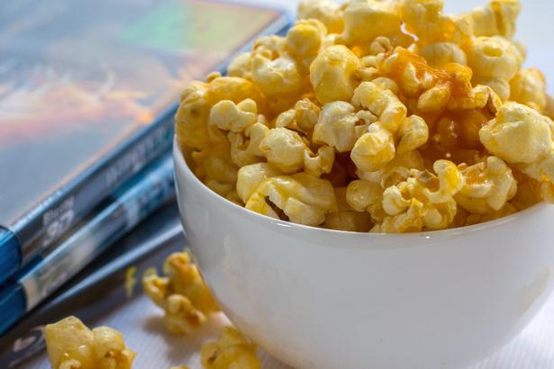bowl of popcorn beside a stack of DVDs